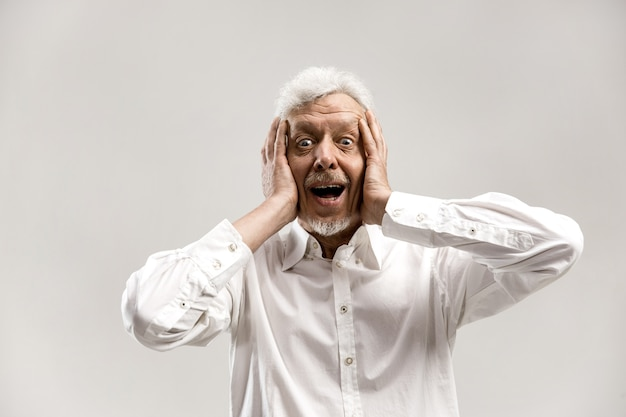 Beeindruckend. senior männliches halblanges porträt auf grauem studiohintergrund. reifer emotional überraschter bärtiger mann, der mit offenem mund steht. menschliche emotionen, gesichtsausdruckkonzept.