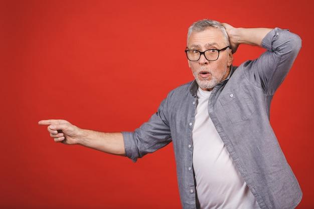 Beeindruckend! unglaublich! alter schockierter älterer mann, der eine brille trägt, mit der hand präsentiert und mit dem finger zeigt.