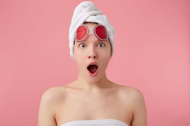 Beeindruckend! unglaubliche neuigkeiten! junges erstauntes mädchen nach spa mit einem handtuch auf dem kopf und einer maske für die augen, mit weit geöffnetem mund und augen, hört neuen klatsch, steht auf.