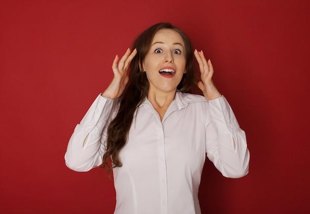 Beeindruckend. weibliches halblanges vorderes porträt lokalisiert auf rotem studiohintergrund. junge emotionale überraschte frau, die mit offenem mund steht. menschliche emotionen, gesichtsausdruckkonzept.