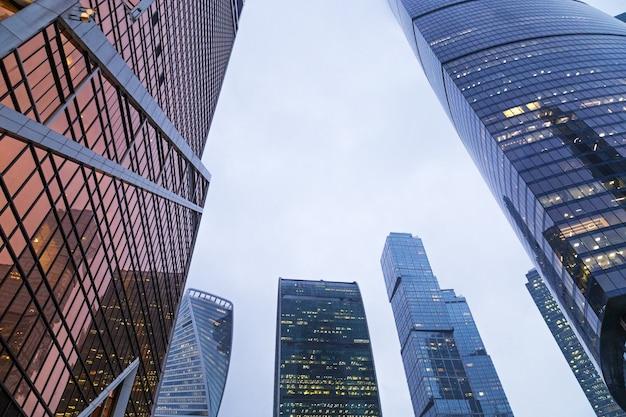 Beeindruckende wolkenkratzer bis zum himmel. blaues glasgebäude aus glas, moderner baustil. wohnungen und büros in riesigen häusern.