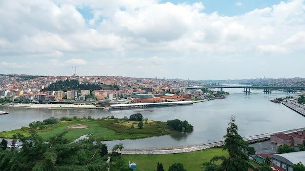 Beeindruckender panoramablick auf die bucht mit ufergegend gegen kulturhauptstadt mit wolkenkratzern unter bewölktem himmel