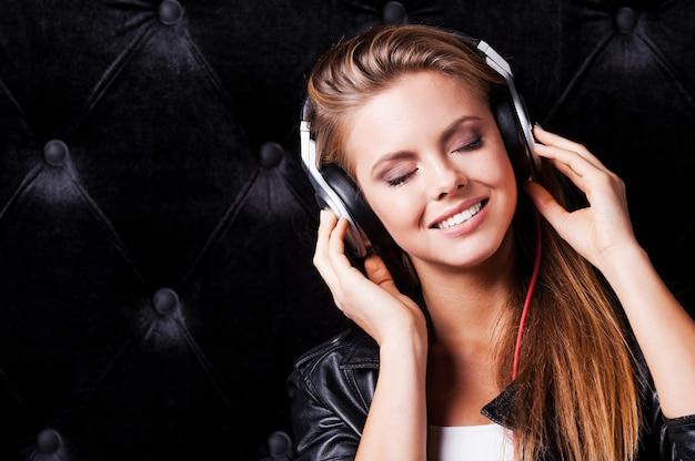 Beeindruckendes lied! schöne junge frau mit make-up und kopfhörern posiert vor schwarzem hintergrund