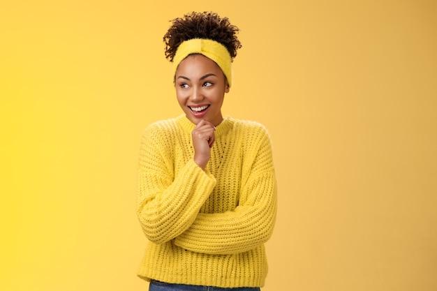 Beeindruckt aufgeregt überrascht glücklich attraktive afroamerikanische lockige mädchen stirnband pullover kichern erstaunt blick links berühren kinn nachdenklich lachende lustige szene, stehend gelber hintergrund.