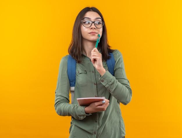Beeindruckt aussehende junge schulfrau mit rucksack mit brille, die ein notizbuch mit stift hält