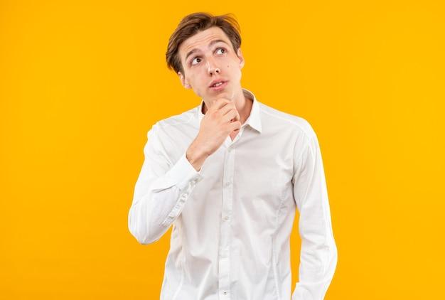 Beeindruckt aussehender junger, gutaussehender kerl, der ein weißes hemd trägt, packte das kinn