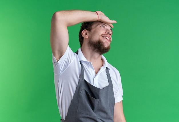 Beeindruckt aussehender junger männlicher friseur in uniform, der die hand auf den kopf legt, isoliert auf grüner wand