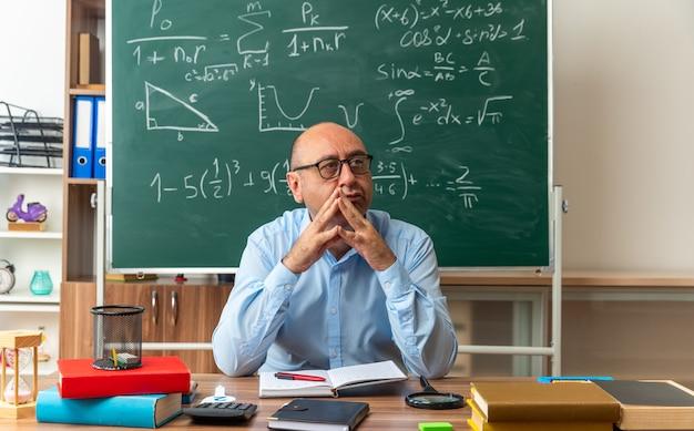 Beeindruckt aussehender männlicher lehrer mittleren alters mit brille sitzt am tisch mit schulsachen, die im klassenzimmer händchen halten