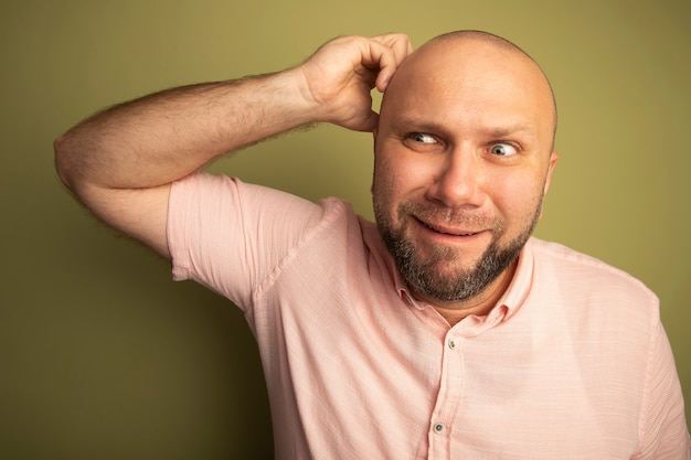 Beeindruckt beim betrachten des kahlen mannes mittleren alters, der rosa kratzendes t-shirt des kopfes trägt