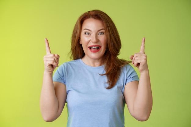Beeindruckt enthusiastisch glücklich fröhlich fröhlich mittelgroße reife frau rotes haar lächelnd erstaunt blick bewunderung freude zeigt mit erhobenen zeigefingern beeindruckende beeindruckende angebot grüne wand