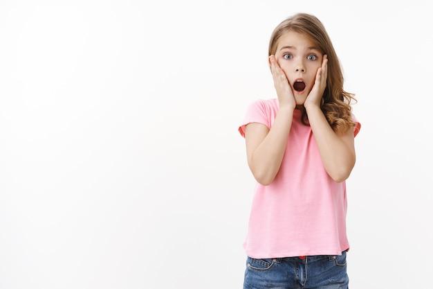 Beeindruckt sprachlos süßes hübsches blondes mädchen in rosa t-shirt, gesicht mit offenem mund erstaunt greifen, kamera erschrocken und schockiert anstarren, kiefer erstaunt fallen lassen, von gruseliger spinne überfallen, weiße wand