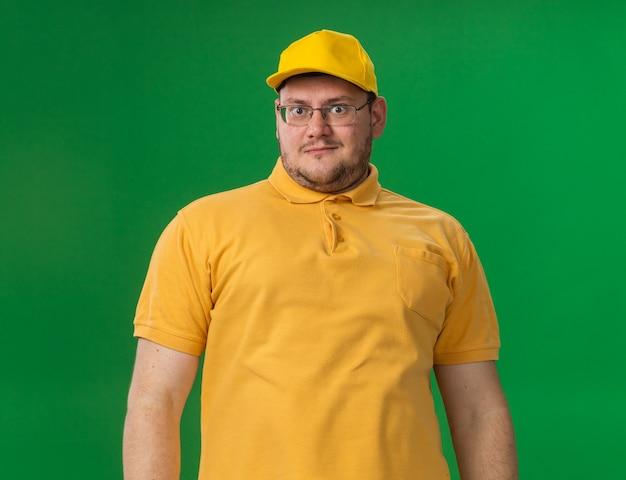 Beeindruckt übergewichtiger junger lieferbote in optischer brille isoliert auf grüner wand mit kopierraum