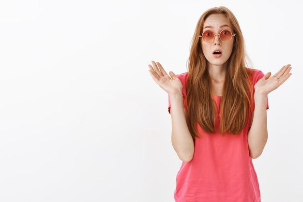 Beeindruckt und erstaunt stilvolles, gut aussehendes rothaariges mädchen mit sommersprossen, die gespreizte handflächen heben und vor nervenkitzel nach luft schnappen und eine unglaubliche und großartige leistung sehen, die mit dem klatschen beginnt