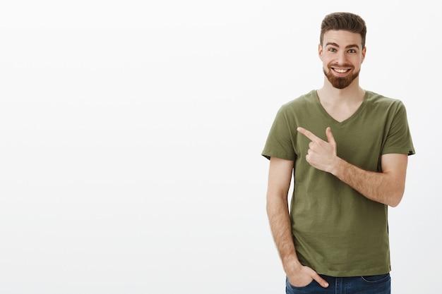 Beeindruckt und überrascht sehr glücklicher bärtiger kerl mit tiefblauen augen im t-shirt, der auf die obere linke ecke oder hinten zeigt, mit einem erfreuten, aufgeregten lächeln, das über die weiße wand von einem unglaublichen produkt erzählt