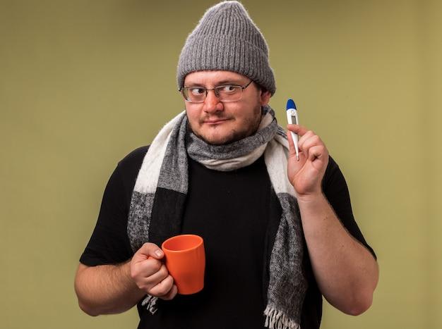 Beeindruckt von der seite eines kranken mannes mittleren alters mit wintermütze und schal, der eine tasse tee mit einem an der olivgrünen wand isolierten thermometer hält