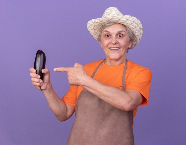 Beeindruckte ältere gärtnerin, die gartenhut hält und auf aubergine auf purpur zeigt