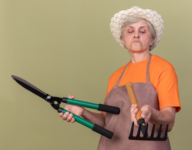 Beeindruckte ältere gärtnerin, die gartenhut trägt, die gartenschere hält und rechen lokalisiert auf olivgrüner wand mit kopienraum betrachtet