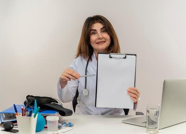Beeindruckte ärztin mittleren alters, die medizinische robe und stethoskop trägt, sitzt am schreibtisch mit medizinischen werkzeugen und laptop, die mit stift auf zwischenablage halten und zeigen