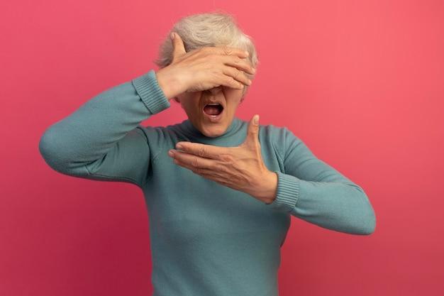 Beeindruckte alte frau mit blauem rollkragenpullover, die die augen mit der hand bedeckt und eine andere hand in der nähe des gesichts hält, isoliert auf rosa wand