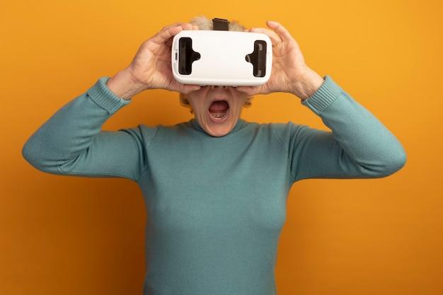Beeindruckte alte frau mit blauem rollkragenpullover und vr-headset, das vr-headset greift und nach vorne isoliert auf oranger wand schaut