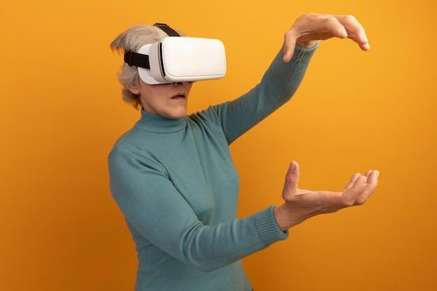 Beeindruckte alte frau mit blauem rollkragenpullover und vr-headset gibt vor, etwas zu halten, das es isoliert auf orangefarbener wand mit kopienraum betrachtet