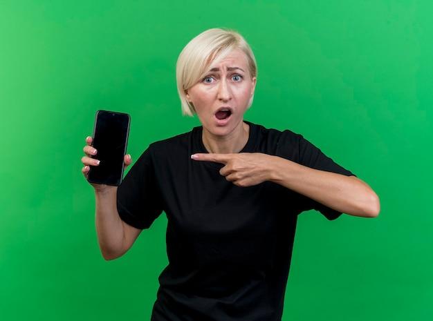 Beeindruckte blonde frau mittleren alters, die nach vorne schaut und handy zeigt, das lokal auf grüner wand zeigt