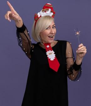 Beeindruckte blonde frau mittleren alters, die weihnachtsmann-stirnband und krawatte hält, die feiertagswunderkerze hält, die kamera zeigt, die oben auf lila hintergrund zeigt