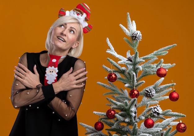 Beeindruckte blonde frau mittleren alters, die weihnachtsmann-stirnband und krawatte trägt, die nahe verziertem weihnachtsbaum stehen und hände verschränkt auf armen halten, die lokal auf orangefarbenem hintergrund suchen