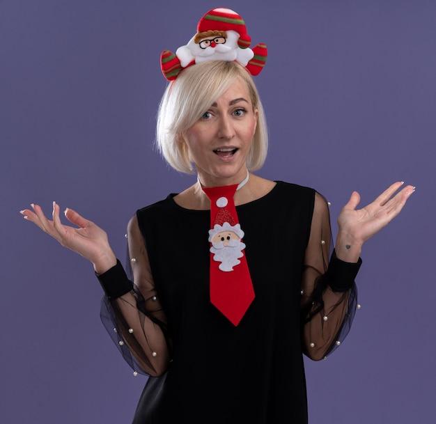 Beeindruckte blonde frau mittleren alters, die weihnachtsmann-stirnband und krawatte trägt und kamera betrachtet, die leere hände lokalisiert auf lila hintergrund zeigt