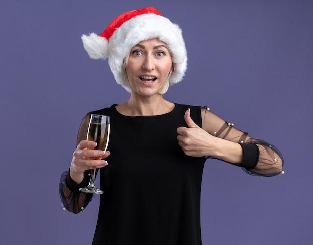 Beeindruckte blonde frau mittleren alters, die weihnachtsmütze trägt, die kamera hält, die glas champagner zeigt daumen oben auf lila hintergrund zeigt