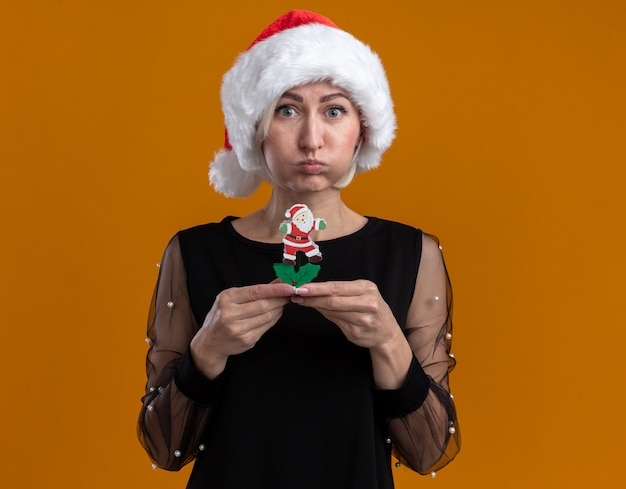 Beeindruckte blonde frau mittleren alters, die weihnachtsmütze trägt und kamera betrachtet, die weihnachtsmann-spielzeug-puffwangen lokalisiert auf orangefarbenem hintergrund hält