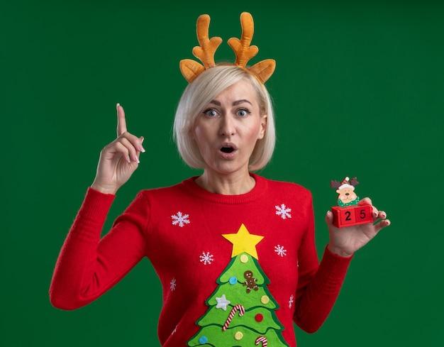 Beeindruckte blonde frau mittleren alters, die weihnachtsrentiergeweih-stirnband und weihnachtspullover trägt, die weihnachtsrentierspielzeug mit datum betrachten, das kamera zeigt, die lokal auf grünem hintergrund zeigt
