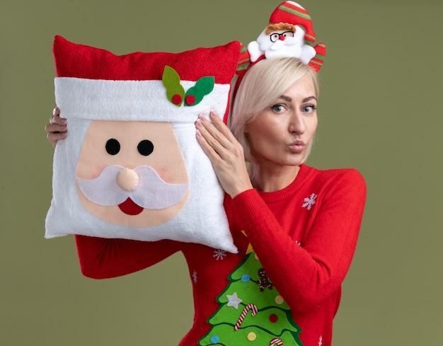 Beeindruckte blonde frau mittleren alters mit weihnachtsmann-stirnband und weihnachtspullover mit weihnachtsmann-kissen, der den kopf berührt und mit geschürzten lippen isoliert auf olivgrüner wand schaut