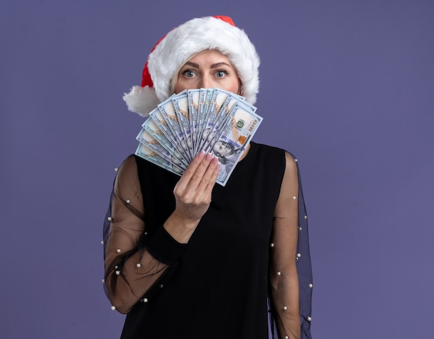 Beeindruckte blonde frau mittleren alters mit weihnachtsmütze, die geld von hinten isoliert auf lila wand mit kopienraum hält