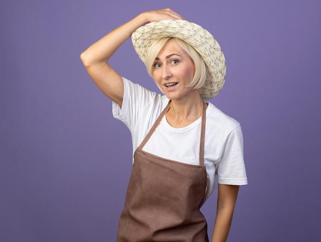 Beeindruckte blonde gärtnerin mittleren alters in uniform mit hut, die hand auf den hut legt