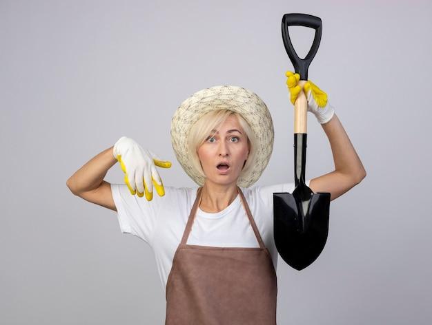 Beeindruckte blonde gärtnerin mittleren alters in uniform mit hut und gartenhandschuhen, die den spaten in der luft halten