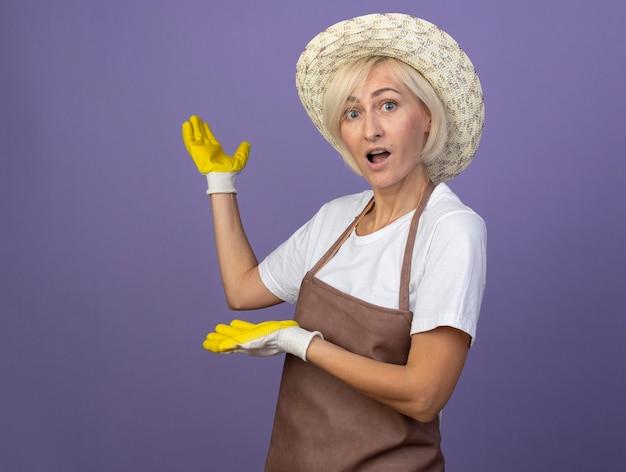 Beeindruckte blonde gärtnerin mittleren alters in uniform mit hut und gartenhandschuhen, die in der profilansicht steht und nach vorne mit den händen nach hinten zeigt