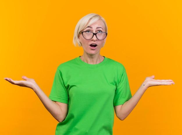 Beeindruckte blonde slawische frau mittleren alters, die eine brille trägt, die leere hände zeigt, die lokal auf gelbe wand schauen