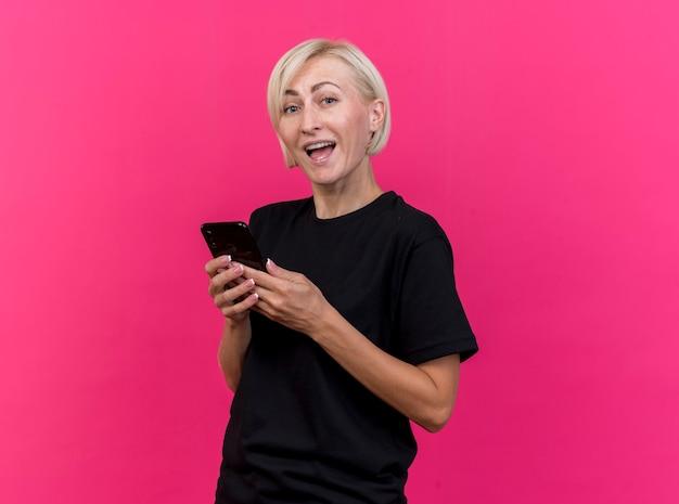 Beeindruckte blonde slawische frau mittleren alters, die in der profilansicht steht und handy lokalisiert auf purpurroter wand mit kopienraum hält