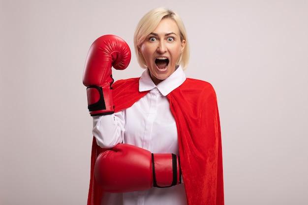 Beeindruckte blonde superheldin mittleren alters im roten umhang mit boxhandschuhen, die die faust schreiend in der luft hält