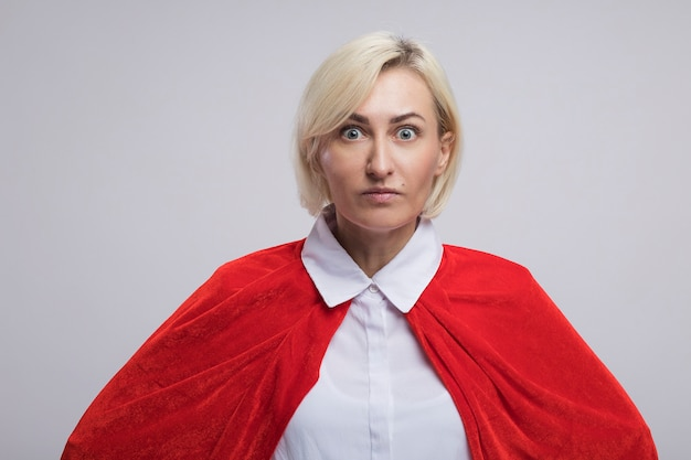 Beeindruckte blonde superheldin mittleren alters im roten umhang
