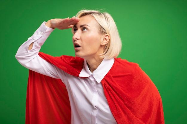 Beeindruckte blonde superheldin mittleren alters in rotem umhang, die die hand auf der stirn hält und seitlich in die ferne schaut, isoliert auf grüner wand