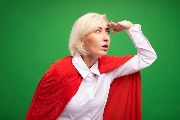 Beeindruckte blonde superheldin mittleren alters in rotem umhang, die die hand auf der stirn hält und seitlich in die ferne schaut