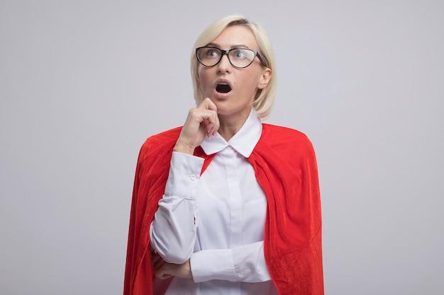 Beeindruckte blonde superheldin mittleren alters in rotem umhang mit brille, die das kinn berührt, das isoliert auf weißer wand mit kopienraum nach oben schaut