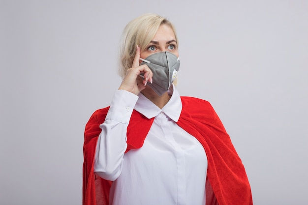 Beeindruckte blonde superheldin mittleren alters in rotem umhang mit schutzmaske, die auf die seite schaut und denkgeste einzeln auf weißer wand mit kopierraum macht