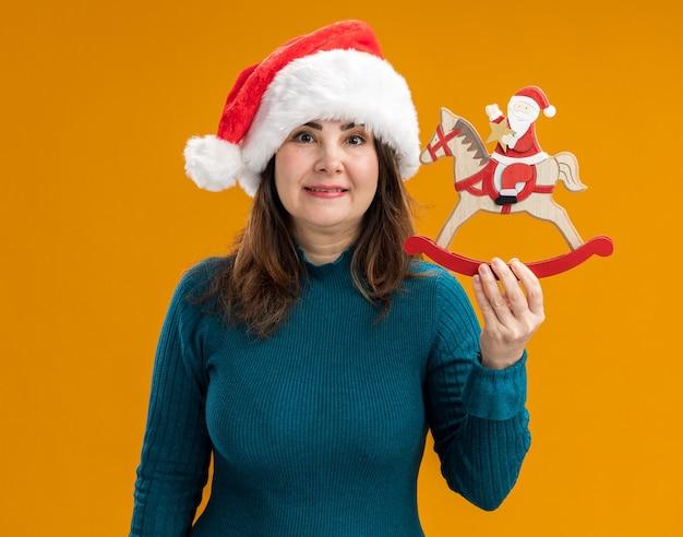 Beeindruckte erwachsene kaukasische frau mit weihnachtsmütze, die weihnachtsmann auf schaukelpferdedekoration lokalisiert auf orange hintergrund mit kopienraum hält