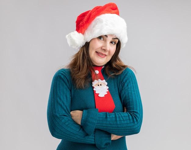 Beeindruckte erwachsene kaukasische frau mit weihnachtsmütze und weihnachtsmann-krawatte, die mit verschränkten armen steht, isoliert auf weißer wand mit kopierraum