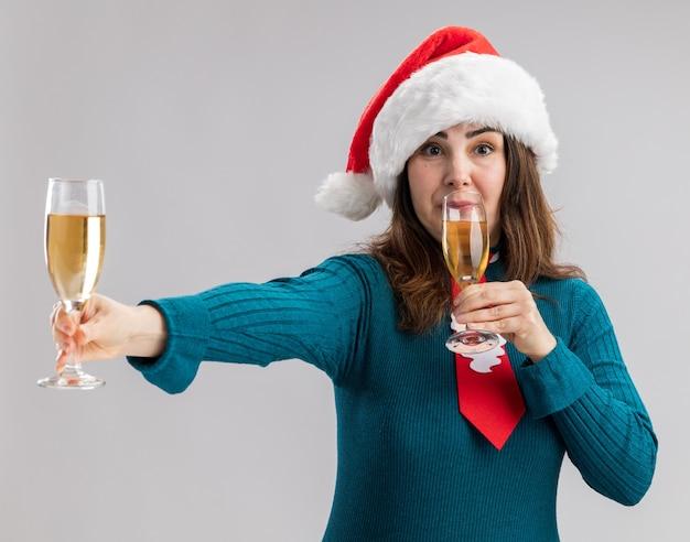 Beeindruckte erwachsene kaukasische frau mit weihnachtsmütze und weihnachtsmann-krawatte mit gläsern champagner isoliert auf weißer wand mit kopierraum
