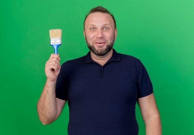 Beeindruckte erwachsene slawische mann suchen halten pinsel isoliert
