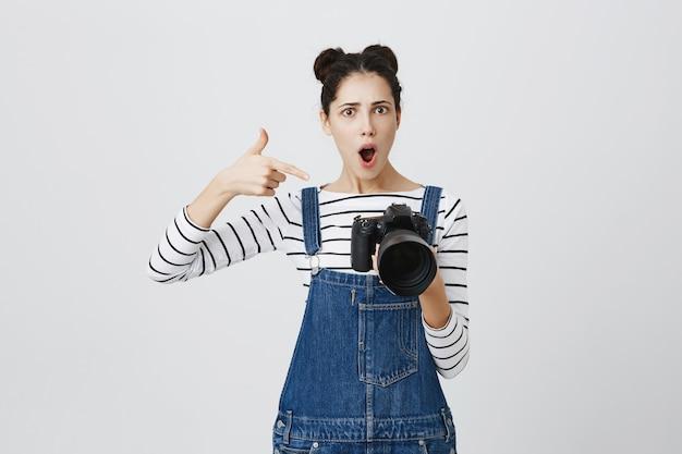 Beeindruckte fotografin zeigt mit dem finger auf die kameraanzeige, lobt tolle aufnahmen, tolle modellarbeit